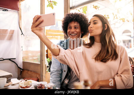 Young woman taking selfie with african man in cafeteria. Young couple looking at  smart phone in cafe. - Stock Photo
