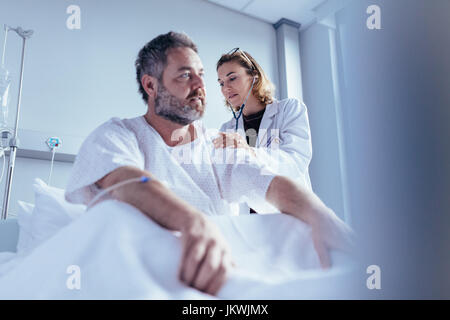 Hospitalised man getting examined by female physician. Doctor checking heart beat of male patient in hospital room.