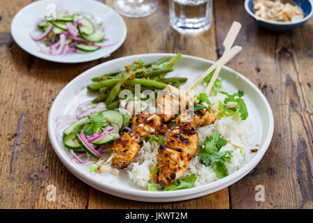 Satay chicken skewers with rice, cucumber salad and green beans