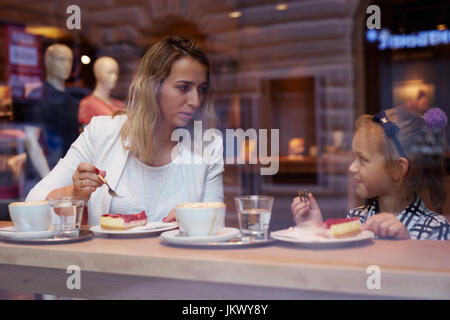 Young mother and daughter spending time in cafe and eating cake - Stock Photo