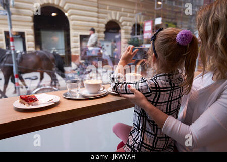 Young mother and daughter spending time in cafe and making photos - Stock Photo