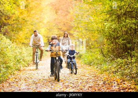 Young family in warm clothes cycling in autumn park - Stock Photo