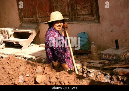 Chinese lady digging a trench in old town Urumqi - Stock Photo