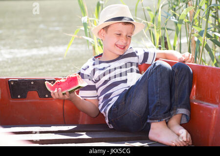 Little cute boy sits in a boat on the river, eats a juicy watermelon and enjoy the beautiful and sunny day - Stock Photo