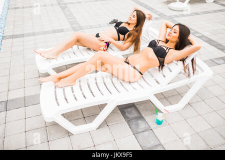 girlfriends clinking glasses with cocktails at the poolside bar - Stock Photo