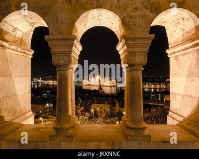 Night view of the famous Hungarian Parliament across the river Danube in Budapest, as seen through the arches of - Stock Photo