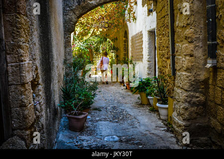 Single female traveler walking past two stray cats in a back alley of the Mediterranean city of Rhodes Greece - Stock Photo