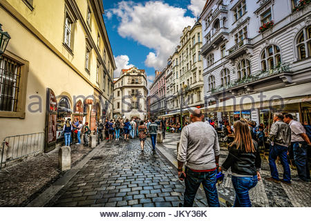 A crowd of tourists sightseeing in the Praha district of Prague on a partly cloudy day in early autumn as they pass - Stock Photo