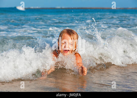 Happy family lifestyle. Baby girl splashing and jumping with fun in breaking waves. Summer travel, water sport outdoor - Stock Photo