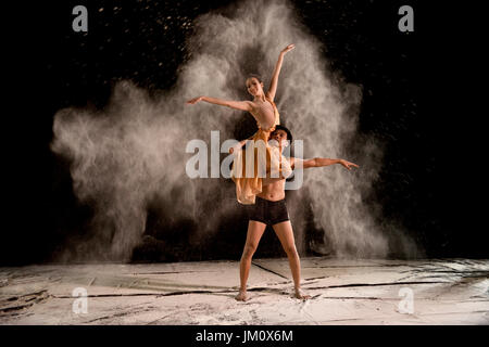 Attractive couple ballet dancer with white powder in the air against black background - Stock Photo