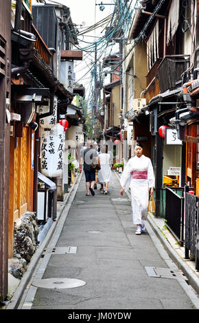 KYOTO, JAPAN - July 24, 2017: Tourists and a woman wearing a fine kimono brave the summer heat in an alleyway in - Stock Photo