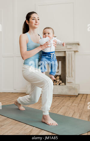 Mother with baby boy practicing yoga on yoga mat at home - Stock Photo