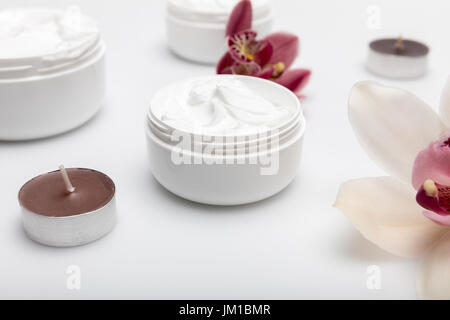 Close-up view of organic cream in containers with orchids and candles isolated on white - Stock Photo