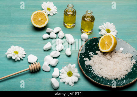 Top view of sea salt, oil in bottles, sliced lemon and chamomiles on wooden table top - Stock Photo