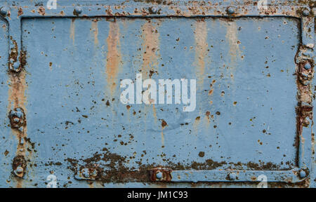 Old blue rusted metal plate with rivets - Stock Photo