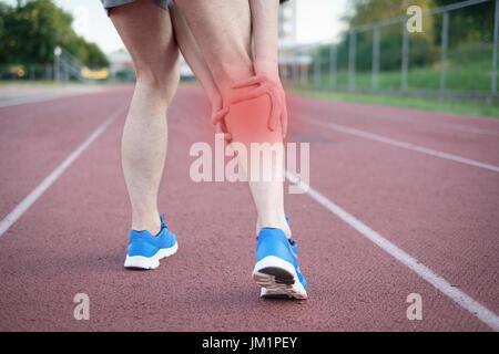 Running sportsman feeling pain after having his knee injured - Stock Photo