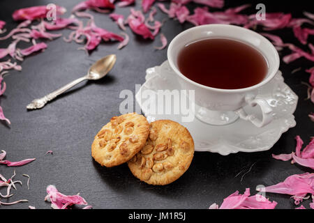 Black coffee or tea in white cup with two peanut cookies and peony petals scattered around - Stock Photo