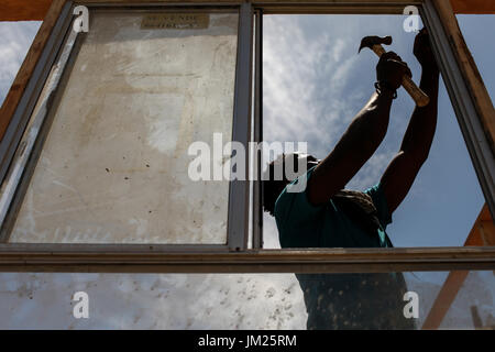 Tijuana, Baja California, Mexico. 19th July, 2017. A Haitian migrant installs a window of a structure along a dry - Stock Photo