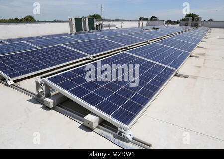 PV solar panels on the flat roof of a new primary school in Essex, UK - Stock Photo