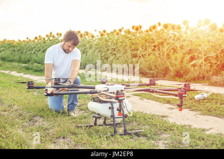 Young engineer preparing agriculture drone before flying - Stock Photo