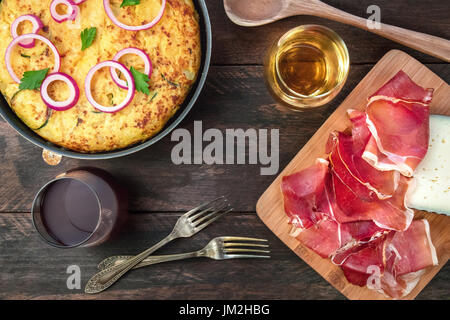 Spanish tortilla in tortillera, with wine, jamon, and cheese - Stock Photo