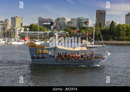 Black Spirit Pirate Cruise Ship with tourists sailing in False Creek across Granville Island Seawall in Vancouver - Stock Photo