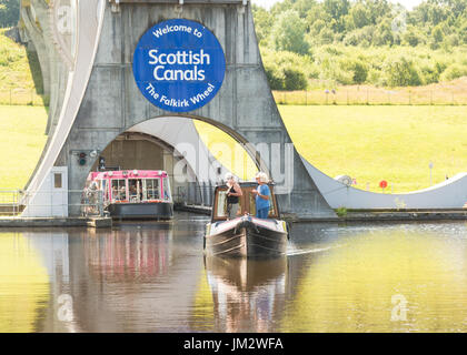 Falkirk Wheel, Scotland - private pleasure narowboat and the pink visitor boat leaving the bottom of the wheel - Stock Photo