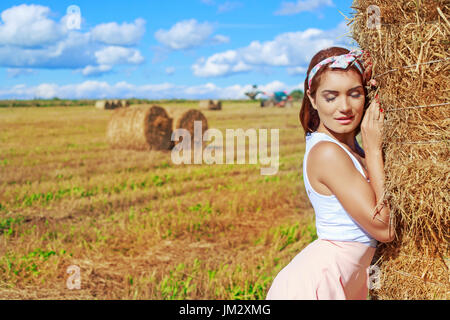beautiful woman in the harvested  wheat field in august on a sunny day - Stock Photo