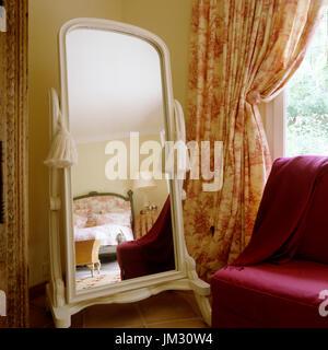 Feminine bedroom reflected in mirror - Stock Photo