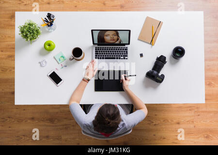 woman with camera working on laptop at table - Stock Photo