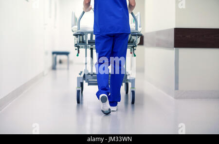 nurse carrying hospital gurney to emergency room - Stock Photo