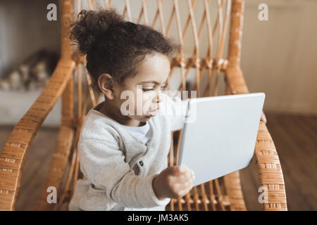 adorable little african american girl using digital tablet and sitting on rocking chair at home - Stock Photo