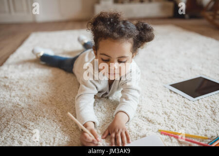 adorable little african american girl drawing with pencils and lying on carpet at home - Stock Photo