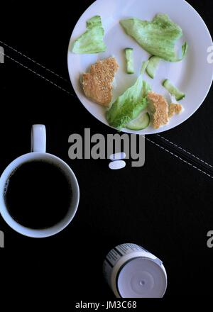 Focus on Drug pills or medicine tablets with a plate of leftover food and a cup of black coffee - Stock Photo