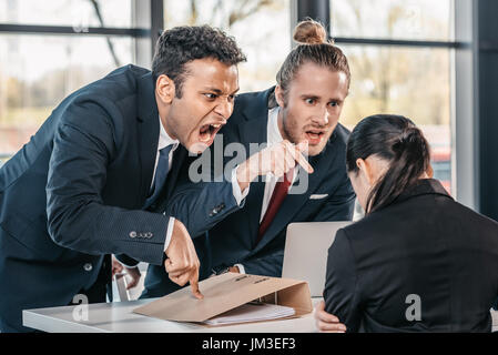 young emotional businesspeople in formalwear arguing at meeting in office, business team meeting - Stock Photo