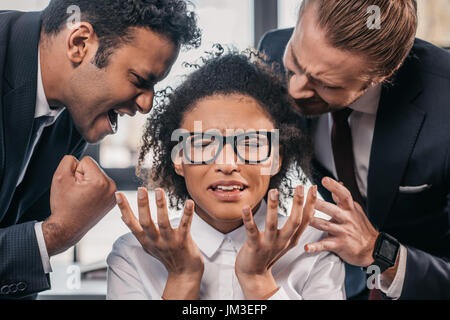 two emotional businessmen in formalwear screaming on businesswoman in office, multicultural business team - Stock Photo