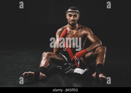 smiling muay thai fighter swathing hand in bandage isolated on black - Stock Photo