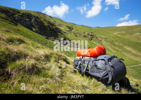 Mountain hiking backpack equipment on the grass with mountain landscape background - Stock Photo