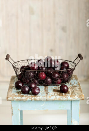 Ripe plums in a basket on a wooden background. Selective focus. - Stock Photo