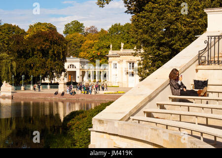 Warsaw, Poland - October 2, 2014: Young girl relaxing on a bench of The Amphitheatre in Lazienki Krolewskie park - Stock Photo