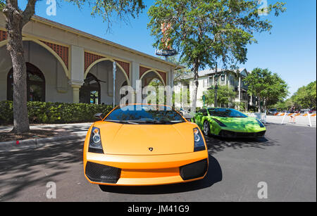 A pair of Lamborghini cars parked outside a restaurant in Front Street at the annual exotic car show in Celebration - Stock Photo