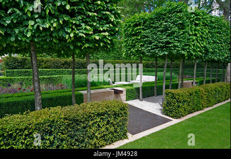 A classical garden with an avenue of yew, box and hornbeam leading to a water feature and sculpture - Stock Photo