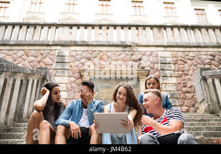 Group of attractive teenage students sitting on stone steps in front of university holding tablet, reading or watching - Stock Photo
