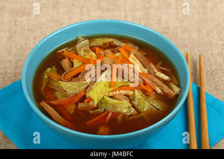 Portion of Asian noodle ramen miso soup with beef meat and vegetables in ceramic blue bowl on table with chopsticks, - Stock Photo