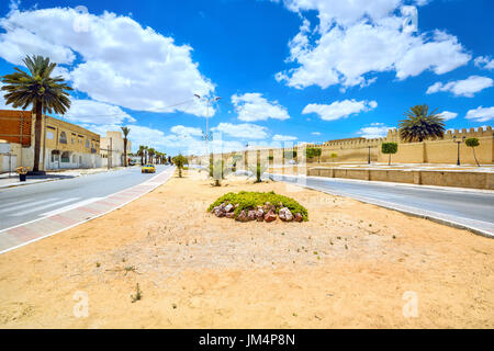 Cityscape with road and wall of Great Mosque in Kairouan city. Tunisia, North Africa - Stock Photo