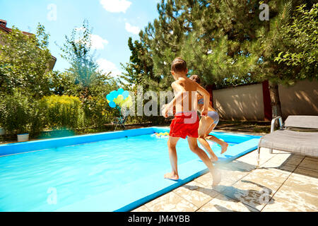 Children jump into the pool in the summer - Stock Photo