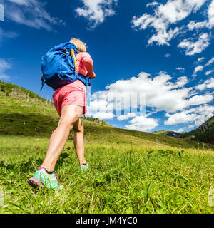 Woman hiking and walking in mountains with backpack. Travel and trekking in beautiful summer nature, inspiring health - Stock Photo