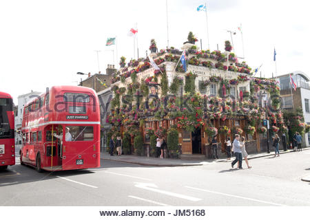 The Churchill Arms pub in Kensington, London in full Bloom with over a hundred hanging baskets, window boxes and - Stock Photo