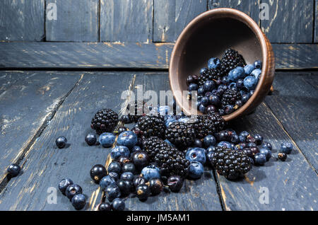 Composition from forest berries. Berries are scattered from the plate. The berries are dark in color. Berries on - Stock Photo