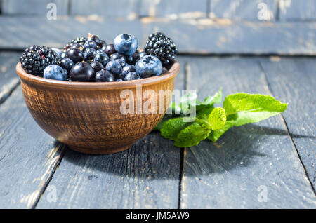 Sweet forest berries in a clay bowl. Rural style. - Stock Photo